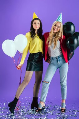 Studio shot of blissful girls in party hats holding air balloons on purple background stock vector