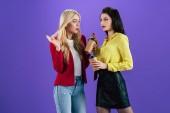 Lányok érdeklődéssel beszél, és a kávéfogyasztás lila háttér