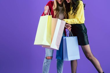 Cropped view of girls looking in shopping bags on purple background
