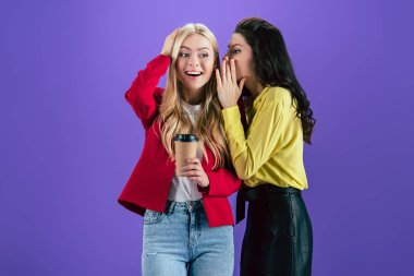 Stylish brunette woman whispering secret to friend on purple background