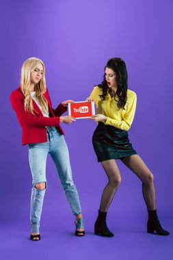 Unhappy girls holding digital tablet with youtube app on screen on purple background