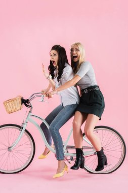 Shocked girls screaming while riding bike on pink background