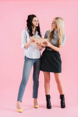 Studio shot of girls with book looking at each other on pink background