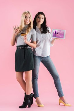 Amazing girls posing with credit card and digital tablet with shopping app on screen on pink background