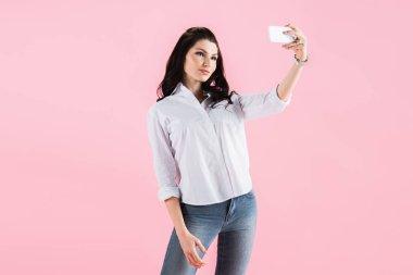 Beautiful brunette girl taking selfie on smartphone, isolated on pink stock vector