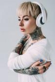 Fotografie atraktivní žena s tetováním, poslech hudby ve sluchátkách izolované Grey