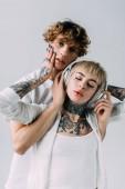 Fotografie pohledný muž držící sluchátka dívka s tetováním poslech hudby se zavřenýma očima izolované Grey