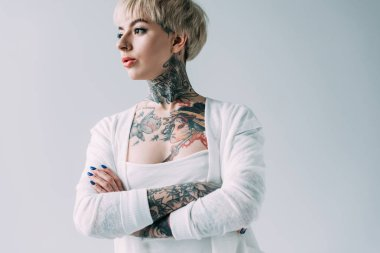attractive woman with tattoos standing with crossed arms isolated on grey