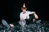Fotografie muž s kudrnatými vlasy sedí v strany SZP s disco koule izolované na černém pozadí