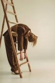 Fotografia donna alla moda in stile vintage che propone vicino alla scaletta di legno su beige