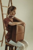 elegantní mladá žena drží kožený váček a poblíž žebřík izolované na béžové