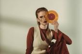 atraktivní mladá žena držící vintage vinyl záznam na béžové