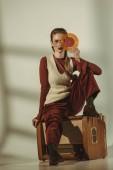 schöne junge Frau hält die Vinyl-Schallplatte und sitzen auf Vintage tv auf Beige