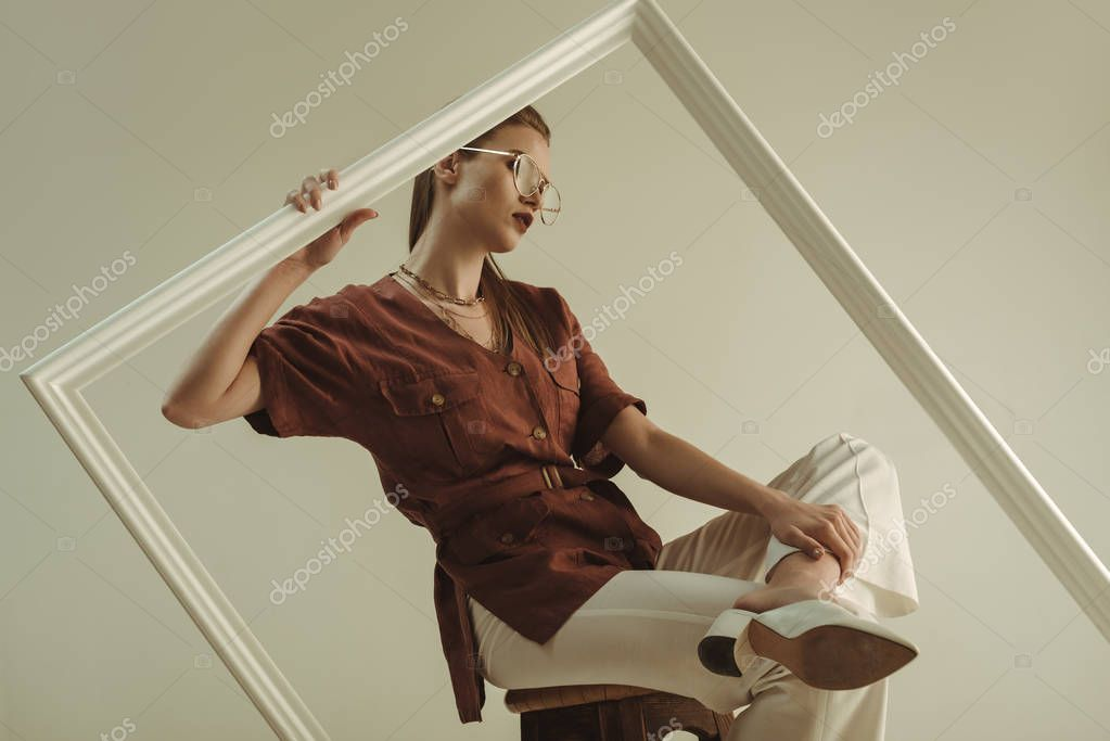 Fashionable girl in vintage outfit posing on stool with big white frame isolated on beige stock vector