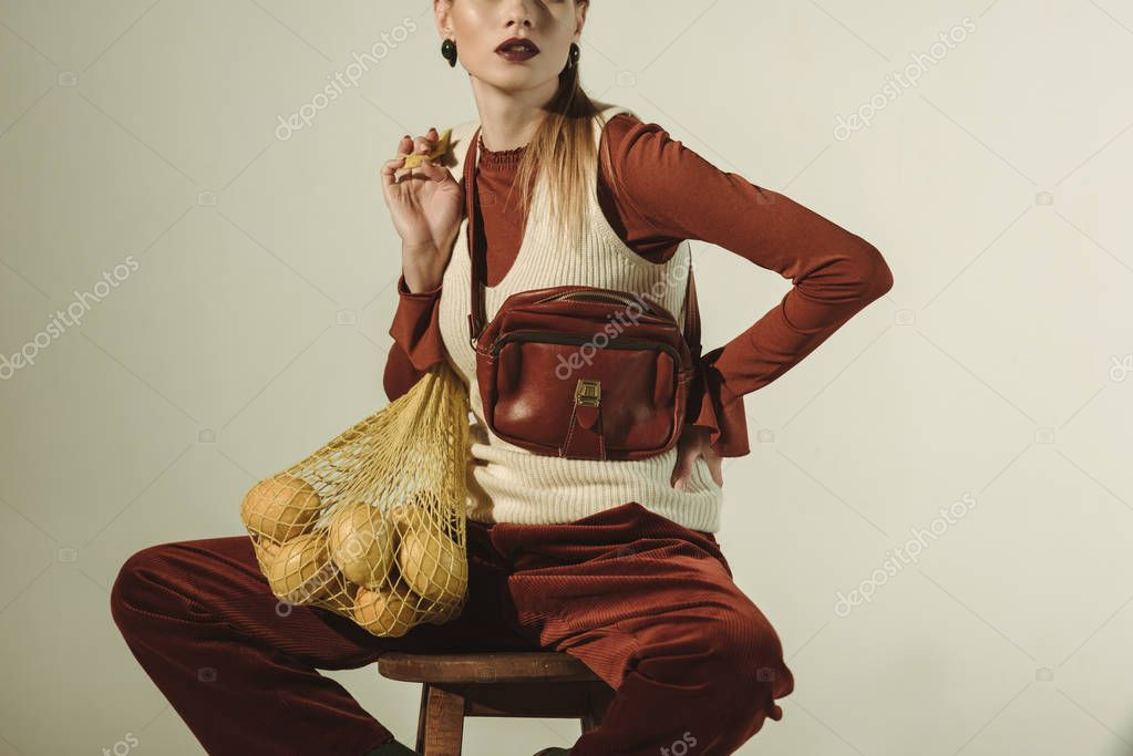 Cropped view of fashionable girl sitting on stool with lemons in string bag isolated on beige stock vector