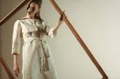 stylová holka v bílé módní oblečení pózuje s velkým dřevěným rámem izolované na béžové