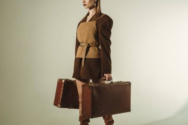 cropped view of stylish woman holding retro travel bags on beige