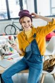 krásná usměvavá žena návrháře sedí na stole a pomocí smartphone v podkroví úřadu