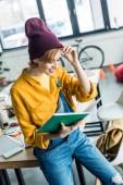 beautiful smiling female designer holding notebook in loft office