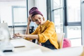Fotografie stressed young female it specialist using laptop in loft office
