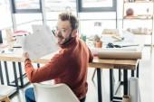Fotografie hezký mužský architekt sedí u stolu a práci na plány, které v podkroví úřadu