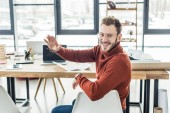 male architect sitting at computer desk, waving and working on blueprints in loft office