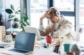 Fotografie schön es Spezialist für Kopfhörer sitzt am Schreibtisch und Laptop in Loftbüro