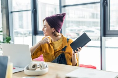 smiling young female it specialist with notebook using laptop in loft office