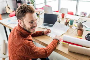 handsome smiling male architect sitting at desk and working on blueprints in loft office