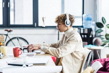 handsome it specialist in headphones sitting at desk and using laptop in loft office