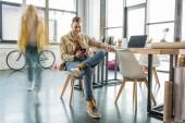 mužské architekt sedí a pomocí smartphone s kolegou v pohybu rozostření na pozadí v podkroví úřadu