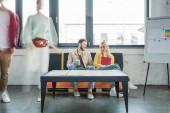 ženské a mužské příležitostné podnikatelé sedí na gauči a mají diskuse v podkroví úřadu s kolegy v pohybu rozostření na pozadí