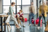 Fotografia concentrati businesspeople casual femminile e maschile seduto e con direttiva in ufficio loft con colleghi in motion blur su priorità bassa