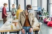 Fotografie männliche Designer in Vr Kopfhörer mit virtual-Reality Erfahrung in Loftbüro mit Kollegen im Hintergrund