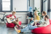 group of friends sitting on bean bag chairs with coffee to go and playing guitar
