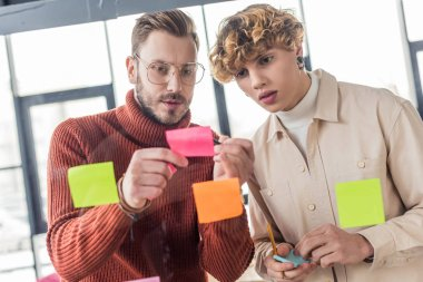 handsome casual businessmen putting colorful sticky notes on glass window in office