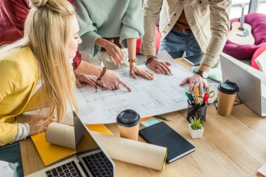 group of female and male architects working on blueprint at desk with coffee to go in loft office