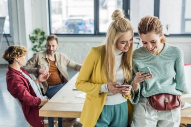 beautiful smiling casual businesswomen using smartphones in loft office with colleagues on background