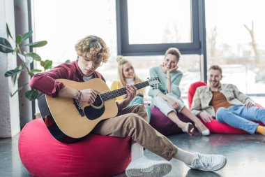 group of friends sitting on bean bag chairs and playing guitar