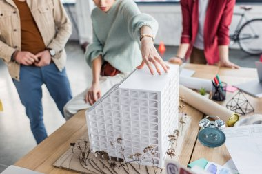 cropped view of group of female and male architects working together on house model in loft office