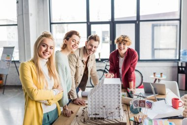 smiling group of female and male architects working together on house model in loft office