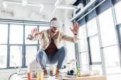 překvapený muž architekt gestikuloval rukama a mít virtuální reality zkušenosti v podkroví úřadu