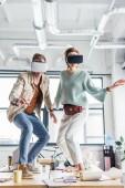weibliche und männliche Designer gestikulieren mit den Händen während mit virtuellen Realität erleben Sie in loft-Büro
