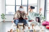 Fotografie aufgeregt, weibliche und männliche Architekten gestikulieren mit den Händen während mit virtueller Realität in Loftbüro erleben