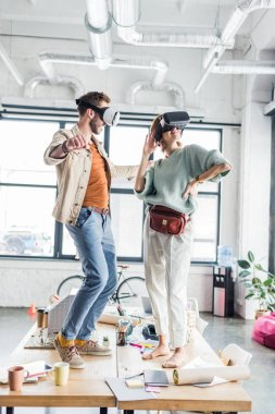 female and male architects wearing vr headset, gesturing with hands and having virtual reality experience in loft office