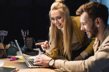 smiling female and male it specialists using laptop in office