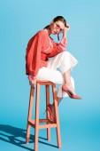 atraktivní stylová žena v coral žije trendy oblečení a pózuje na stoličce na modré sluneční brýle