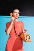 módní model v životní korálové šaty pózuje s rotační telefon na modré