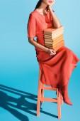oříznutý pohled stylové ženy žít korálové šaty hospodářství knihy a sedí na stoličce na modré