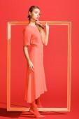 divatos fiatal nő divatos ruhában pózol a coral élő nagy kerettel. Pantone szín az évben 2019 fogalom